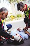 Ambulance man taking care of injured man lying on the floor