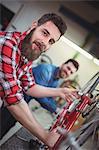 Portrait of mechanic repairing a bicycle in his workshop