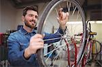 Mechanic repairing a bicycle wheel in his workshop