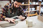 Focused man working at table in workshop