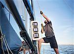 Man adjusting sailing equipment on sailboat