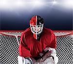 Portrait determined hockey goalie protecting goal net