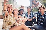 Smiling teenage friends posing for selfie on sunny urban street