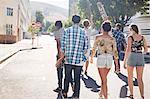 Teenage friends with skateboards walking on sunny urban street