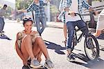 Enthusiastic teenage girl skateboarding with friends on sunny urban street