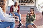 Teenage girls using camera phone at skate park