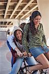Playful teenage girls riding BMX bicycle at skate park