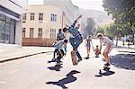 Teenage friends skateboarding on sunny urban street