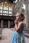 Little girl praying in ruined church