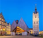 Belgium, Flanders, Ghent (Gent). Het Belfort van Gent, 14th century belfry, and Stadshal, City Pavilion, designed by architects Robbrecht & Daem / Marie-José Van Hee, at dusk.
