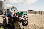 Portrait of farmer riding quadbike at field
