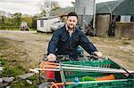 Portrait of young farmer riding quadbike on field against barn