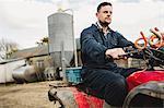 Smart farmer riding quadbike on field against silo