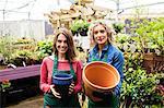Portrait of female florists holding pot in garden centre