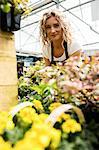 Portrait of female florist checking flower in garden centre
