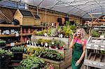 Female florist talking on mobile phone in garden centre
