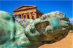 Fallen Icarus Sculpture by Igor Mitoraj in front of Temple of Concordia at Valle dei Templi in Ancient Greek City at Agrigento, Sicily, Italy