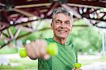 Portrait of senior man weight lifting dumbbells under bridge