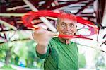 Senior man throwing flying ring under bridge