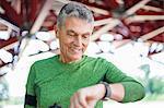 Senior male runner looking at smartwatch under bridge