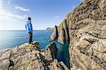 Man on rocks looking at ocean, Vagar, Faroe Islands