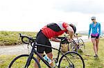 Cyclists fixing saddle on roadside