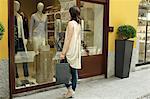 Female shopper looking in boutique window, Milan, Italy
