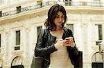Woman reading smartphone text in Galleria Vittorio Emanuele II, Milan, Italy