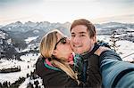 Hiking couple taking selfie overlooking snow covered Allgau Alps, Bavaria, Germany