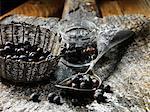 Juniper berries in small glass jar, metal vintage spoon and woven basket, rustic wooden chopping board