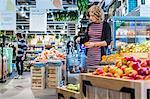 Woman buying oranges while carrying shopping basket in supermarket