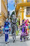 Cuba, Havana, Habana Vieja.  Colourful stilt walkers march down a street in Habana Vieja.