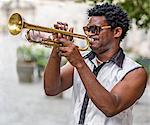 Cuba, Havana, Plaza de San Francisco de Asis.  A Cuban trumpet player entertains passers by in Plaza de San Francisco de Asis.