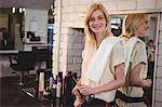 Portrait of smiling female hairdresser holding scissor in salon