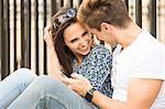Happy young couple sitting on sidewalk, London, UK