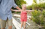 Girl with father stepping along tree trunk at Lake Ontario, Oshawa, Canada