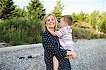 Mid adult woman carrying and hugging small son at Lake Ontario, Oshawa, Canada