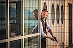 Man in business attire poised behind corner with handgun, Cagliari, Sardinia, Italy