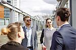 Businessmen and businesswomen having discussion on city footbridge, London, UK