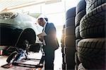 Senior business owner inspecting car repairs in garage