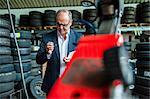 Senior male business owner examining tyre valve in repair garage