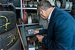 Senior male business owner testing tyre pressure machine in repair garage