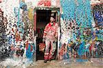 Male ship painter leaning against paint splattered doorway
