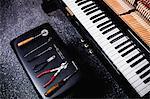 Close-up of repairing tools and old piano keyboard