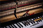 Close-up of repairing tools kept on old piano keyboard at workshop