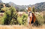Man hiking looking away at view of mountains, Malibu Canyon, California, USA
