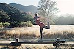 Woman by mountains doing stretching exercises, Malibu, California, USA