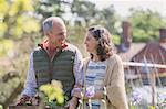 Smiling couple shopping in plant nursery garden