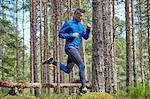 Runner jumping over fallen log on trail in woods