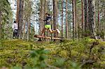 Runner jumping over fallen log in woods